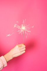 Close up of female hand with burning Christmas sparkler on pink background.