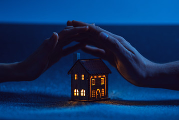home protection. male and female hand on a small house in which the windows glow with warm light