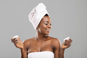 Beuty portrait of smiling black woman holding jar of face cream