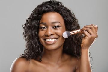 Fototapete - Attractive black girl using brush tool, applying blush on face