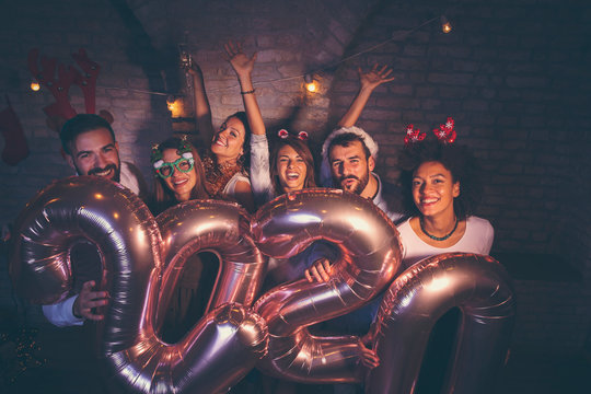 Friends having fun at New Years party midnight countdown