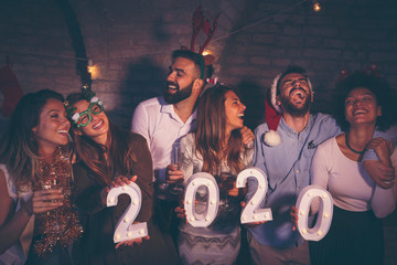 People holding illuminative numbers 2020 at New Years party