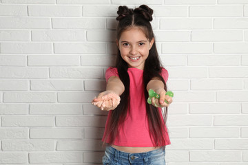 Little girl with slime near white brick wall