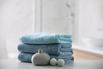 Obraz Stack of fresh towels, soap dispenser and bath bombs on table indoors - fototapety do salonu
