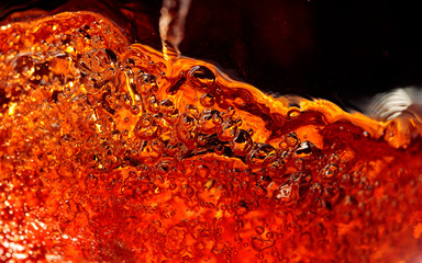 Alcoholic drink on a dark background, abstract splashing.