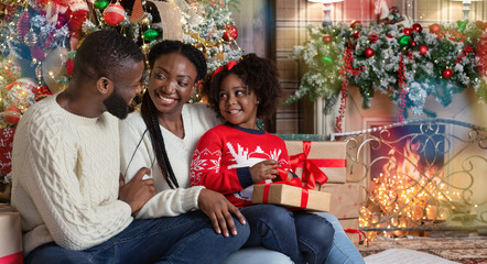 Happy black couple and their little daughter enjoying Christmas together