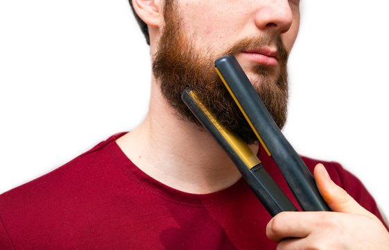 Portrait of man straightened his beard with a straightener, styling his beard on isolated white background