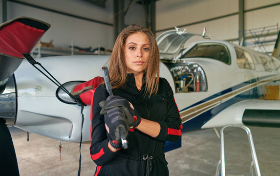 girl technician in the hangar with the plane
