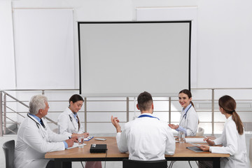 Team of doctors using video projector during conference indoors