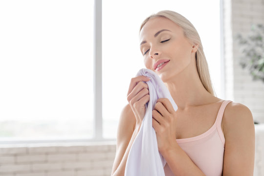 Close up of young woman smelling clean clothes and smiling while doing laundry at home