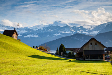 small mountain village and snowy peaks of Alps in the background