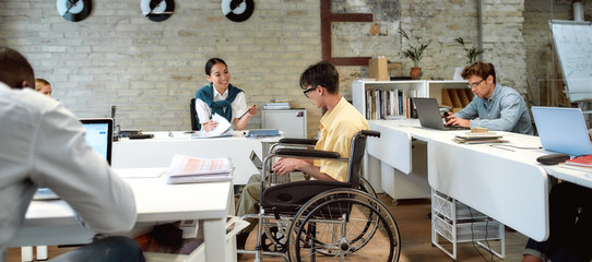 Incredibly doing things rightly. Guy in a wheelchair working in the office