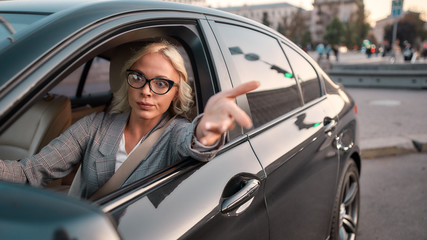 Feeling angry. Portrait of angry business woman gesturing with hands and arguing with somebody while driving a car
