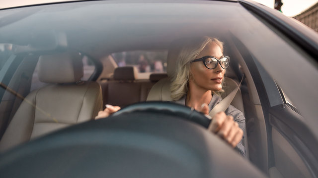 Busy lady. Portrait of confident and attractive young business woman in eyeglasses driving a car and looking in the window
