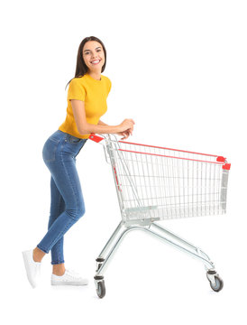 Young woman with empty shopping cart on white background