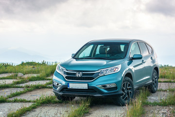 popular family SUV in mountains on a cloudy day. 4th generation of a honda cr-v, in blue color. all wheel drive vehicle on a paved platform. car adventure concept