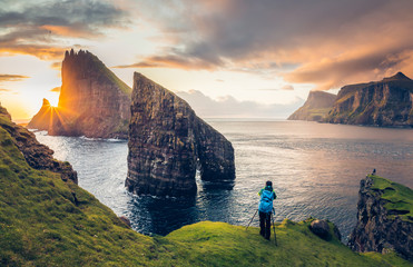 Foto op Aluminium Noord Europa Photographer taking pictures to Drangarnir and Tindhólmur at sunset in the Faroe Islands