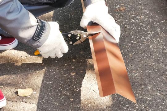 Worker shears sheet of roofing metal. Scissors for metal.