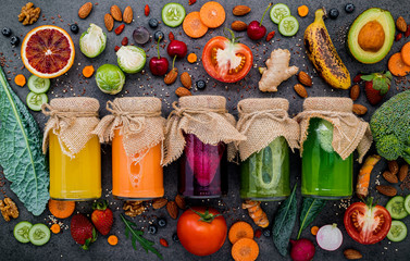 Photo sur Aluminium Jus, Sirop Colourful healthy smoothies and juices in bottles with fresh tropical fruit and superfoods on dark stone background with copy space.