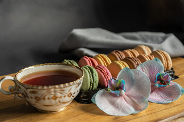 Foto auf Leinwand Macarons Colorful macarons, orchid flowers and a cup of tea put on wood table. Colorful macarons french dessert