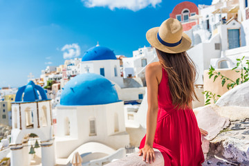 Europe holiday Santorini vacation girl in hat and red dress enjoying view of 3 blue domes famous...