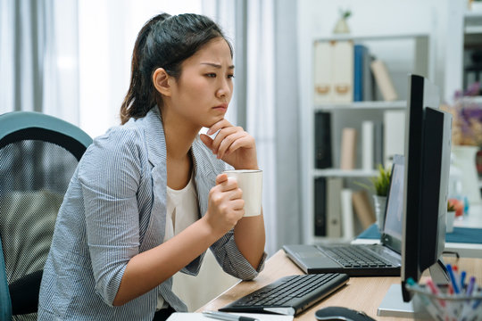 Pensive asian chinese woman in smart casual with desktop computer looking at screen holding coffee cup at home office. young thoughtful lady employee sitting at pc brainstorming during drink tea.