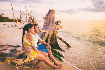 Beautiful sunset honeymoon vacation couple relaxing on summer holiday watching sunset at Florida...