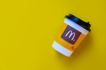Bangkok ,Thailand - March 06 2019 : A paper cup of McDonald's Coffee on yellow background.