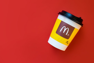 Bangkok ,Thailand - March 06 2019 : A paper cup of McDonald's Coffee on red background.