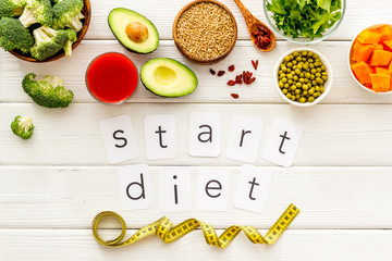 Start diet text near healthy food on white wooden background top view