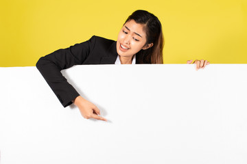Young Asian woman in formal wear smiling and pointing at white blank banner for advertisement campaign against yellow background