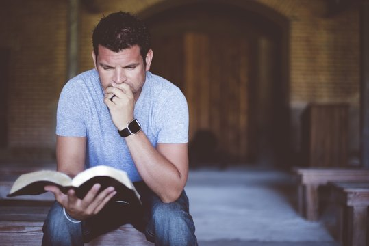 Closeup shot of a male sitting while reading the bible with a blurred background