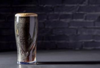 Obraz A dark Irish dry stout beer glass with a black brick on the background - fototapety do salonu