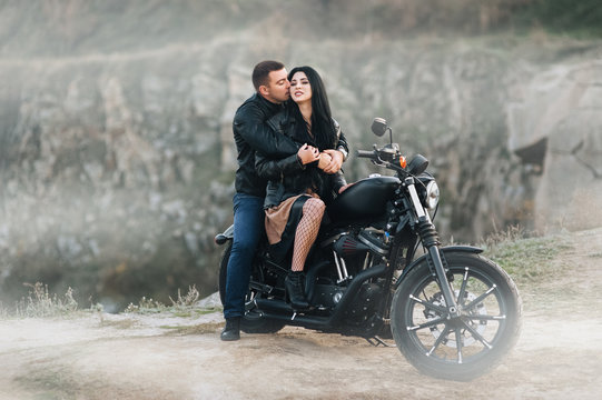 Gorgeous brunette girl in a black dress and a stylish male biker sit and gently hug, kiss on an expensive black motorcycle. Portrait of a couple in love on a background in foggy weather. Love story.
