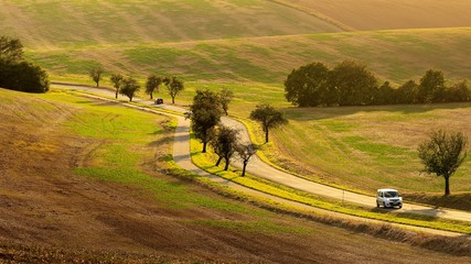 Traveling by car in spring undulating fields of South Moravia in the evening light.
