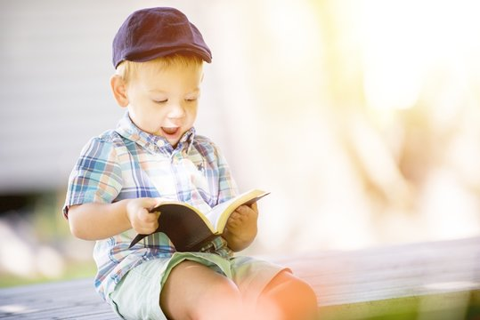 Closeup shot of a surprised child reading the bible with a blurred background