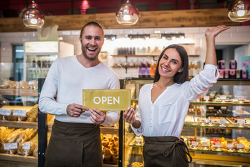 Husband and wife smiling broadly while opening their own bakery