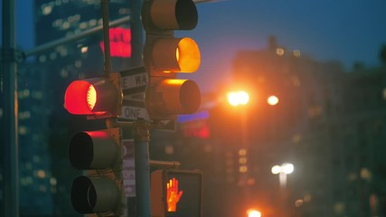 Fotobehang - Traffic light on night street intersection change signals from red to green light. NYC.