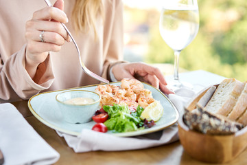 Grilled Argentine shrimp with mango-jalapeno sauce. Lunch in a restaurant, a woman eats delicious and healthy food. Delicious fresh seafood prawns with fresh vegetables and lime. Cream sauce