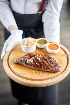 The waiter is holding a plate Grilled striploin steak with Pickled cabbage and two sauces. The strip steak, also called a New York strip. Serving on a wooden Board. Barbecue restaurant menu.