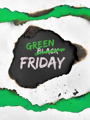 "Green Friday concept with hole burned in white paper. Text ""Black Friday Sale""  with word ""Black"" being crossed out to be replaced with ""Green"" instead."