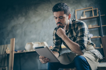 Photo of handsome serious guy holding e-reader website checking email online orders think how to improve service wooden business industry owner woodwork store indoors