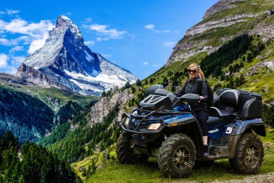 A happy woman riding a quad bike near a lake in the mountains Matterhorn, Zermatt
