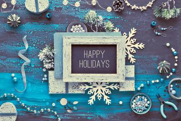 "Creative diy craft hobby. Making handmade jewelry as Christmas gifts. Text ""Happy Holidays"" on decorative blackboard. Flat lay on dark fluid art acrylic background,"