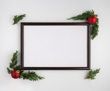 Christmas or New Year composition. Photo frame with copy space, Christmas tree branches and Christmas balls on white background. Flat lay, top view