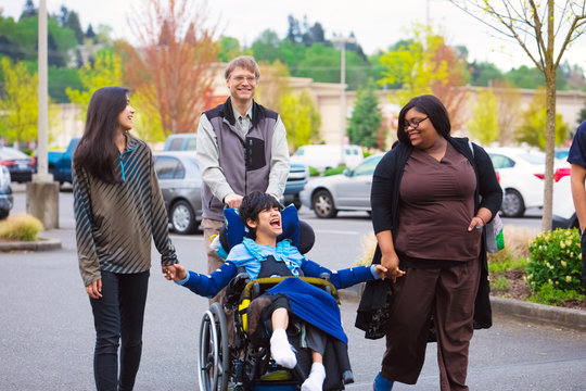 Disabled boy in wheelchair in city  with family and caregiver