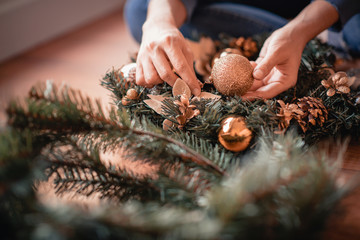 Close up woman making Christmas wreath.