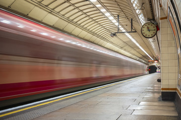 Train arriving in motion at platform of London Underground tube (Gants Hill) station