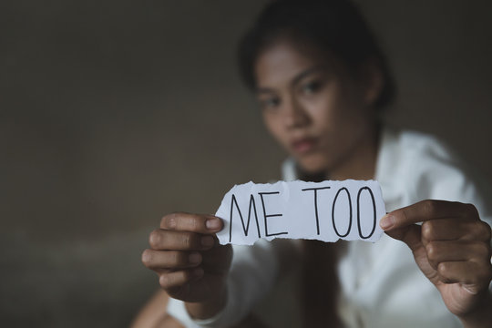women sitting alone with depressed expression and showing a paper with a metoo text. #metoo as a new movement. Ideas to stop violence against women, sexual harassment and rape, human trafficking