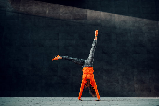 Full length of fit sporty caucasian woman in sportswear doing cartwheel exercise in front of black wall.